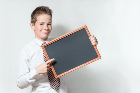 The cute smiling boy teenager in a white shirt and a tie on a gray background specifies a finger in an empty black chalkboard Stock Photo