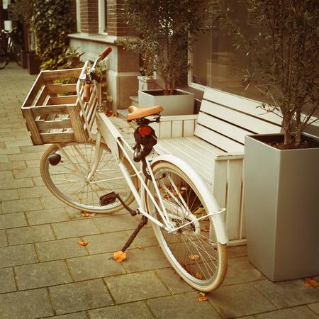 turismo ecologico: Bicicleta de lujo con la cesta estacionado cerca del banco en la calle de Amsterdam