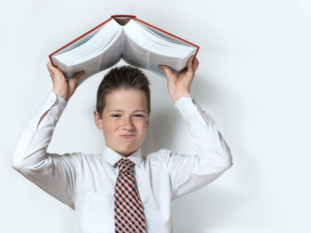 throwaway: The displeased schoolboy teenager in a white shirt and a tie throws down a big red book on the gray background Stock Photo