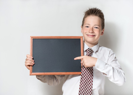 specifies: The nice smiling boy teenager in a white shirt and a tie on a gray background specifies a finger in an empty black board for a chalk