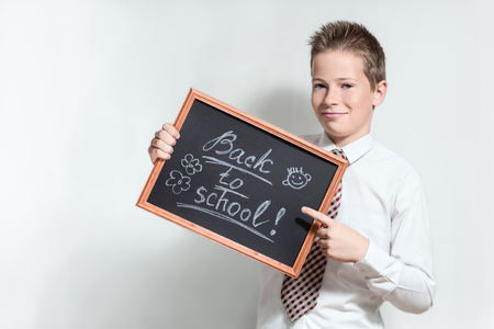 specifies: The nice smiling boy teenager in a white shirt and a tie on a grey background specifies a finger in the black chalkboard with inscription Back to school