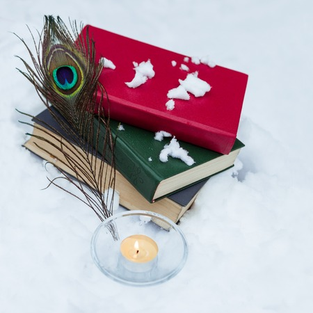 alight: The stack of old books with peacock feather and alight candle on the white snow