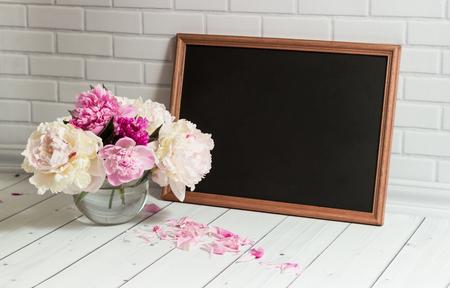 rosa negra: Hermoso ramo de peonías rosas y blancas en el florero de cristal con los pétalos y el pizarrón negro con el lugar vacío para el texto en el ladrillo y la madera de fondo gris claro. Foto de archivo