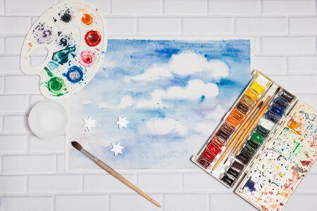 paleta de pintor: Composición con bosquejo de cielo azul y pinturas