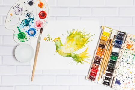palette: Hand drawn watercolor sketch with green dove flying with flower branch and leaves. Lying flat paints, paintbrushes and palette on the white brick background - concept of human creativity, top view. Stock Photo