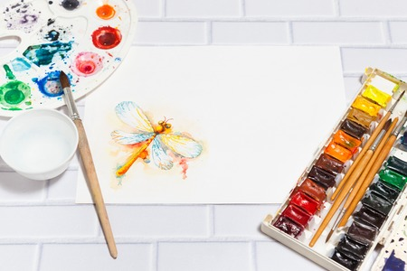 pictorial art: Hand Drawn Sketch of Orange Dragonfly, with lying paints, paintbrushes and palette on the white brick background - concept of human creativity, perspective view. Have an empty place for your text