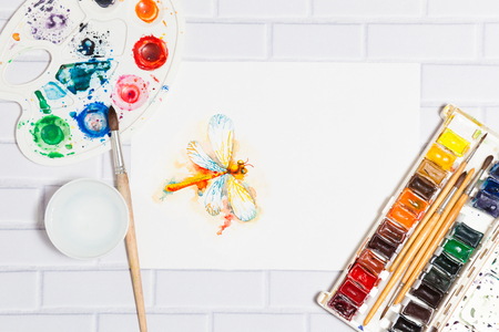 pictorial art: Hand Drawn Sketch of Watercolor Orange Dragonfly,with lying paints, paintbrushes and palette on the white brick background - concept of human creativity,top flat view.Have an empty place for your text Stock Photo