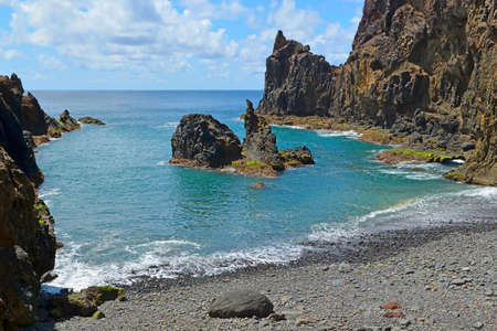 A small secluded pebble beach surrounded by rocks, Praia do Zimbralinho, Porto Santo, Madeira, Portugal. Stock Photo