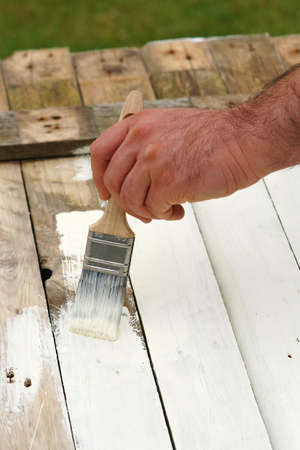 man paints old wood in white color