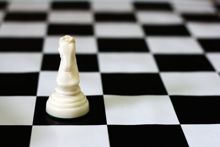 Strategic games; chess; one white knight on chess board Stock Photo