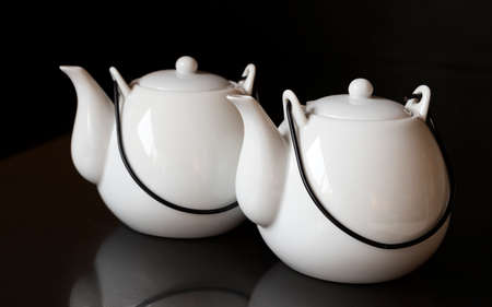 White kettles or tea pots on black background 版權商用圖片