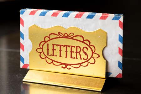 Golden holder with letters, black background Banco de Imagens