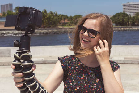 Camera recording a young caucasian female blogger gesturing while making a video
