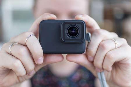 Les mains de la femme se bouchent tenant une petite caméra d'action noire prenant une vidéo ou une photo
