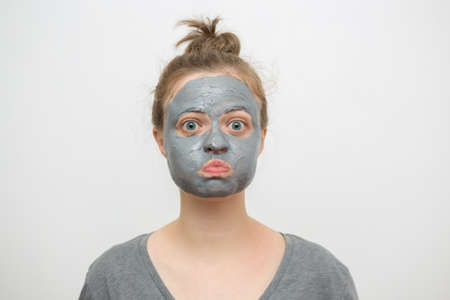 Young caucasian woman with black or grey facial clay mask on her funny face