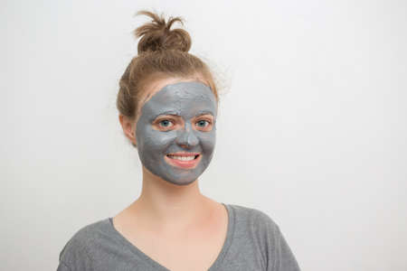 Young caucasian woman with black or grey facial clay mask on her face, smiling Standard-Bild - 124977138