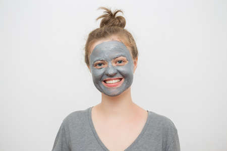 Young caucasian woman with black or grey facial clay mask on her face, smiling Imagens