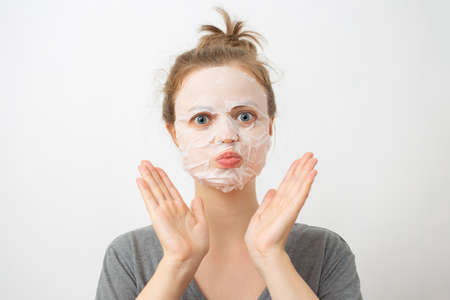Young caucasian woman with wrinkled white facial mask on her face 写真素材 - 124977148