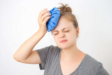 Young caucasian woman holding ice bag to her head, suffering from a headache or fever Stock Photo
