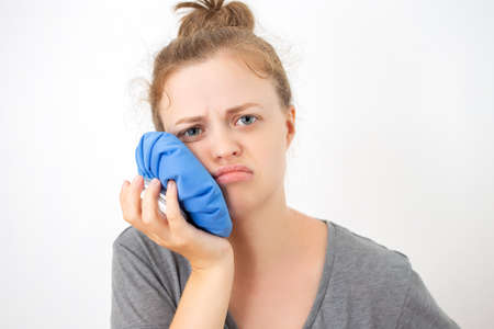 Young caucasian woman holds ice bag to her cheek, suffering from a toothache or dental surgery