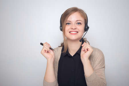 Happy smiling young caucasian woman with headset phone in a call center or office