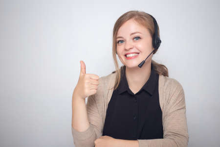 Happy smiling young caucasian woman with headset phone in a call center, thumbs up Imagens