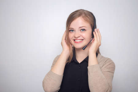 Happy smiling young caucasian woman with headset phone in a call center