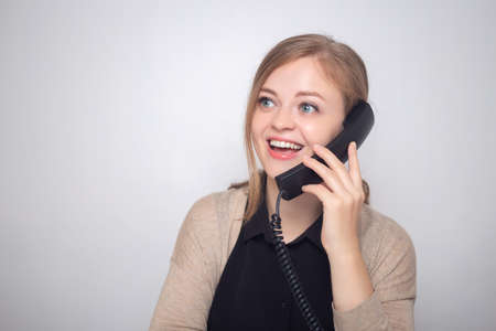 Happy smiling young caucasian woman with land line phone in a call center or office