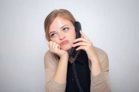 Young caucasian woman is talking on the landline phone, bored, tired or annoyed