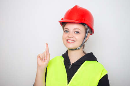 Young caucasian woman wearing red safety hard hat and reflective vest, smiling