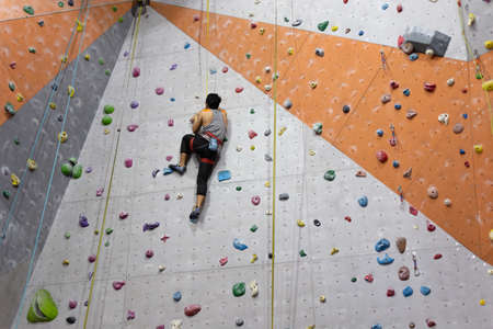 Manila, Philippines - 1, June, 2019: A man climbing up the wall in rock climbing center in Ortigas