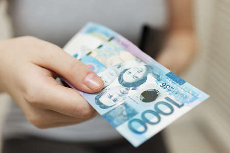 Mano che tiene una banconota in contanti di mille pesos filippini che pagano bollette, procedura di pagamento o tangente, stipendio