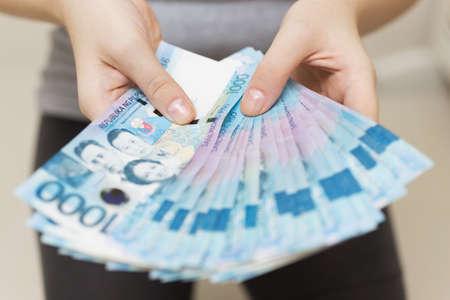 Mani che tengono lo stipendio o il pagamento di un pacco di contanti di mille pesos filippini come se fossero ricchi. Mettiti in mostra, paga le bollette o dai una bustarella. Archivio Fotografico