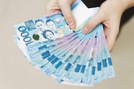 Mani che tengono lo stipendio o il pagamento di un pacco di contanti di mille pesos filippini come se fossero ricchi. Mettiti in mostra, paga le bollette o dai una bustarella.