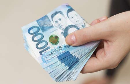 Mano che tiene un pacco piegato di denaro blu in contanti di mille pesos filippini. Dare tangenti, pagare le bollette o ricevere uno stipendio. Giorno di pagamento!