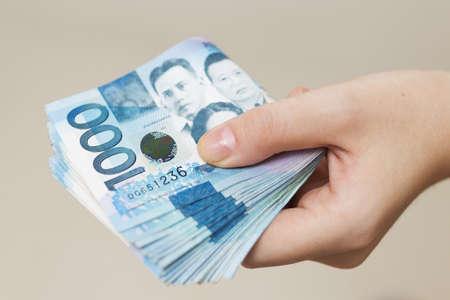 Mano che tiene un pacco piegato di denaro blu in contanti di mille pesos filippini. Dare tangenti, pagare le bollette o ricevere uno stipendio. Giorno di pagamento! Archivio Fotografico