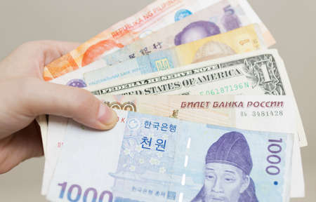 A hand holding money banknotes of different countries: Korean won, Russian rouble, Dollar USA, Chinese RMB yuan and ukraine grivna