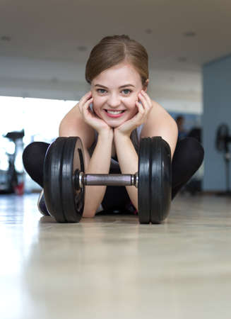 Young caucasian woman girl doing workout with light dumbbells at the gym, lifting weights