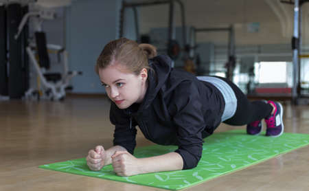 Young caucasian woman  doing plank exercise on her abs at gym