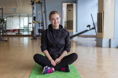 Young caucasian woman sitting on a mat at the gym smiling Imagens