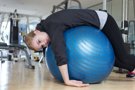 Young caucasian woman lying on blue gymnastic ball looking exhausted, tired, bored and weary at the gym