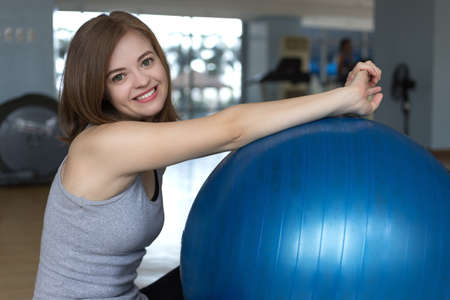 Smiling young caucasian woman girl on blue gymnastic ball at the gym, doing workout or yoga pilates exercise Imagens