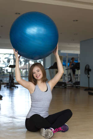 Smiling young caucasian woman girl holding a blue gymnastic ball at the gym, doing workout or yoga pilates exercise Imagens