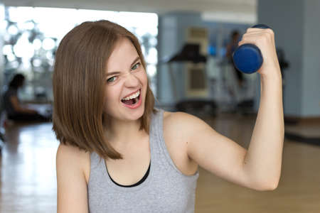 Smiling young caucasian woman girl doing workout with light dumbbells at the gym, lifting weights