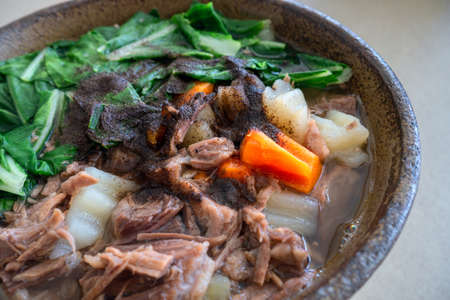 Philippine, Taiwanese or Chinese authentic traditional dish: beef noodle soup with vegetables, closeup