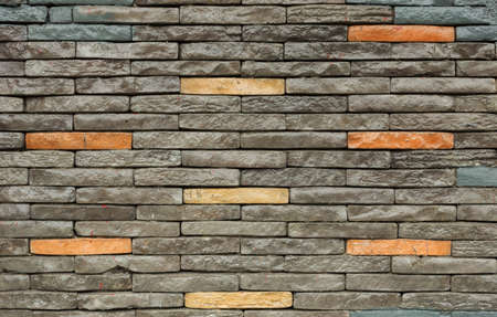 Texture of the brown and grey wall made of stone tile bricks