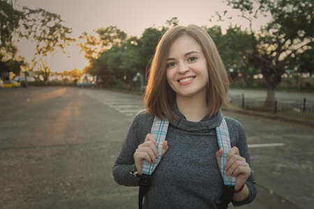 Portrait of young smiling caucasian woman traveller with backpack Imagens