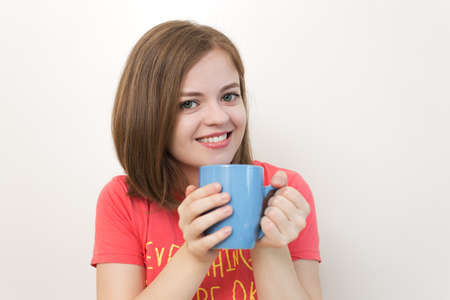 Portrait of smiling young caucasian woman girl holding a mug of coffee with both hands as if saying: Good morning!