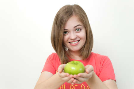Portrait of smiling caucasian woman girl with green apple in her hand. Healthy lifestyle, fruit vegetarian diet.