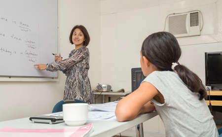 Manila, Philippines - August, 18, 2016: An English female teacher is writing and explaining the rules of English on the white board, teaching a girl Editorial
